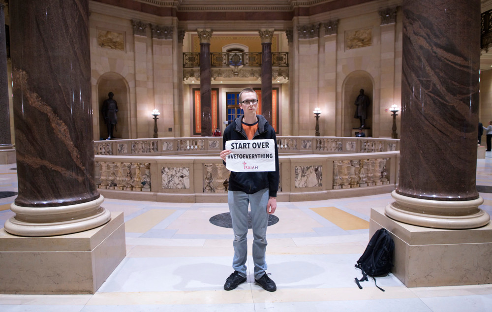 """A lone protester stands outside the House's Chamber with his sign that reads, """"Start Over – Veto Everything"""", but he didn't get his way as the legislature reach a compromise on a $46 billion budget and adjourned the Special Session sine die around 3 A.M. Friday, May 25."""