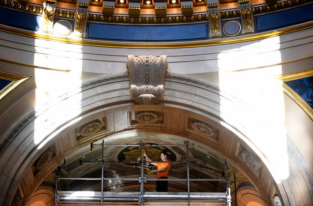 Jeremy Lunn, an art conservator with Conrad Schmitt Studios, examines an old stencil that will be applie to the ceiling on the third-floor of the Capitol.