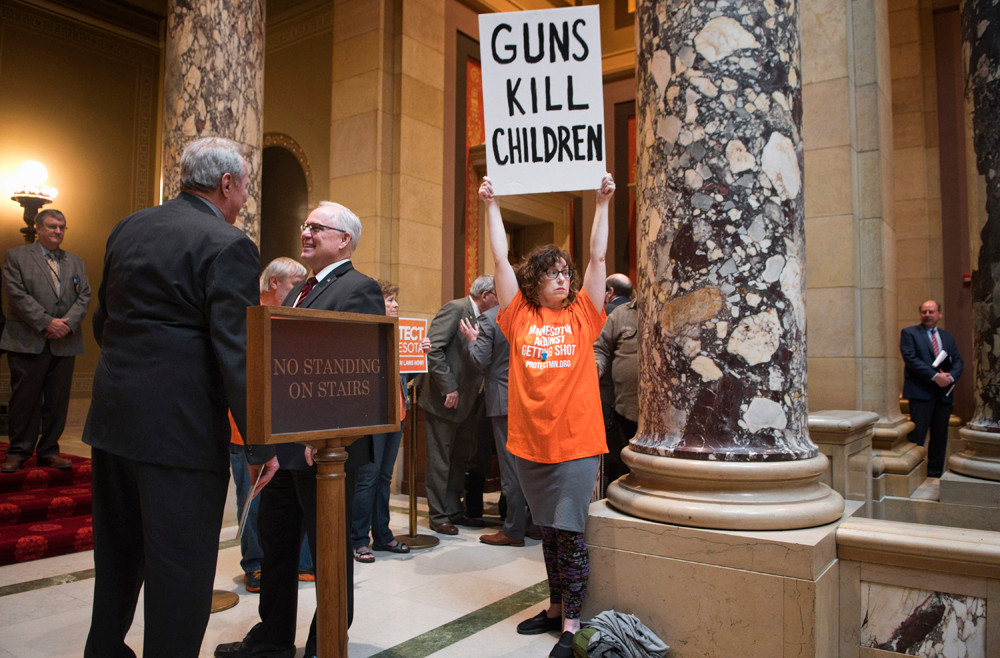 Marti Priest Hopkins, with Protect Minnesota, holds her sign outside the Senate Chamber, Thursday, April 26, as the Senate hears the Omnibus Supplemental Budget Bill. Sen. Ron Latz hopes to attach two gun violence prevention amendments to the judiciary and public safety section of the omnibus bill.