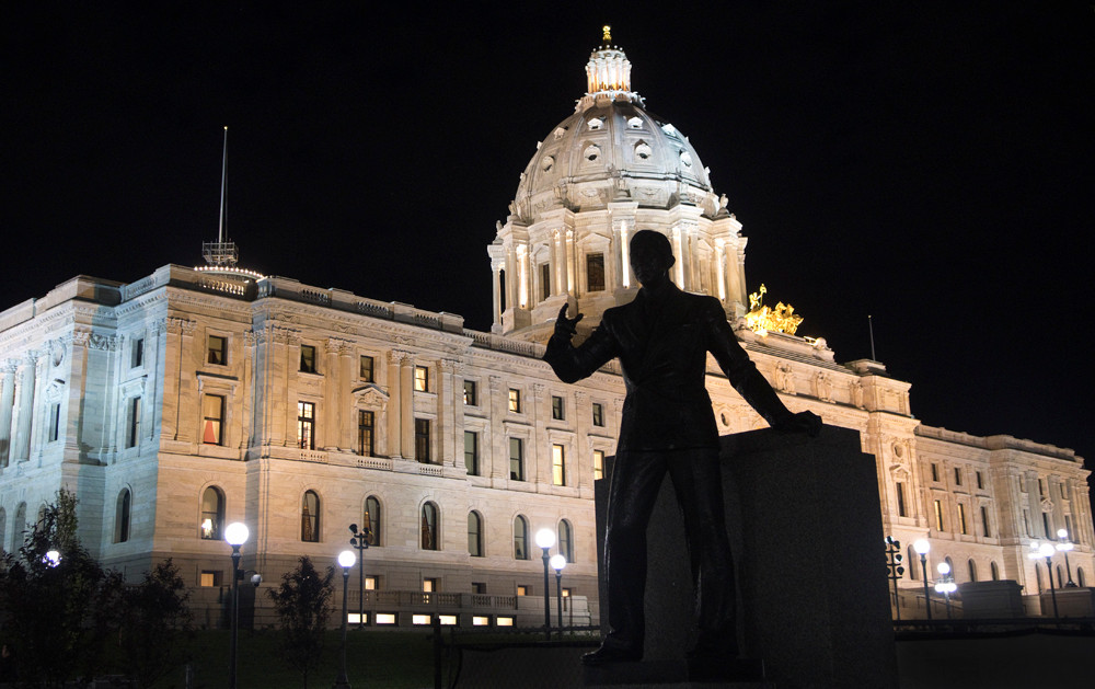 The statue of Gov. Floyd B. Olson is silhouetted against the Capitol as the first twenty-four hours of the Special Session goes into the evening.