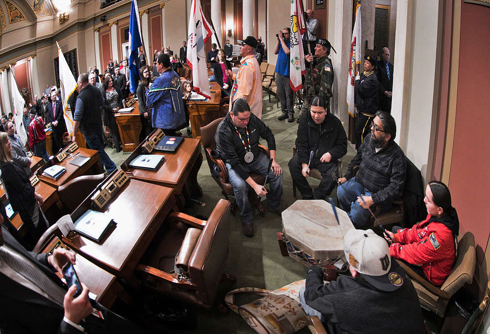 The Red Bone Singers made up of members of Ojibwa, Dakota, Lakota and Ho-chunk bands drum and sing as the flags of Minnesota's eleven Tribal Nations enter the House Chamber to begin Sovereignty Day.