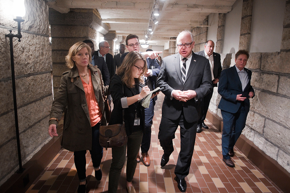 Gov. Tim Walz talks to reports about the budget talks with House and Senate leadership as he makes his way back to his office after appearing at the Water Bar pop-up exhibit in the basement of the Capitol. Conference committees continue to meet while budget talks between Gov. Walz and legislative leaders are not scheduled to meet until May 12. The House and Senate must adjourn the legislative session on May 20.