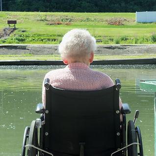 Senior enjoying sunshine by pond