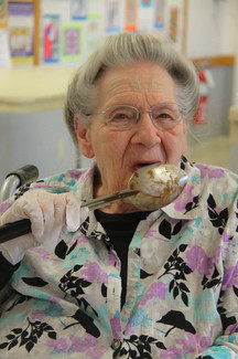 senior licking spoon after cooking activity