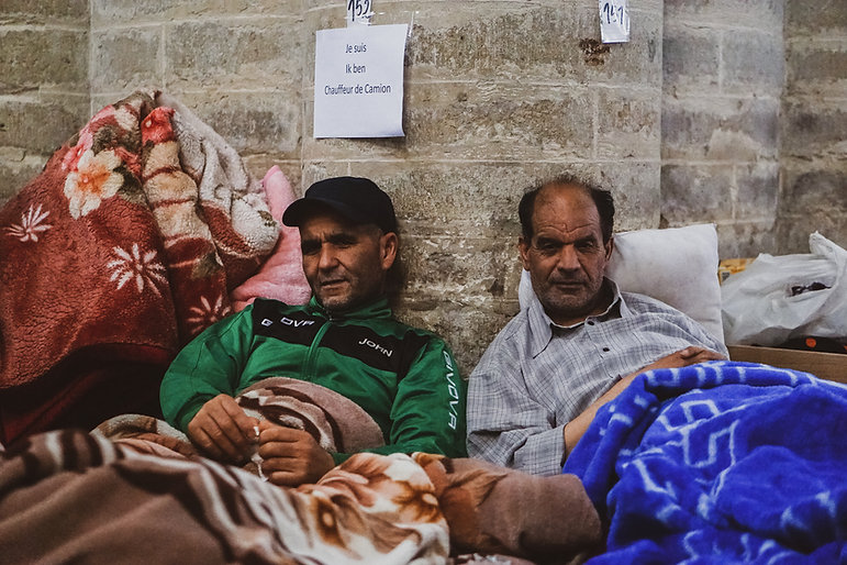 Two men rest during the hunger strike where each activist put a paper with their job in Be