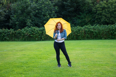 Lucy in a denim jacket holding a yellow umbrella. She is looking towards the camera and slightly leaning to the side