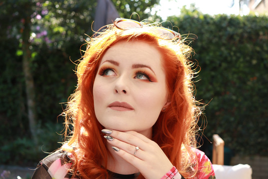 Lucy Edwards looking up with her hand under her chin