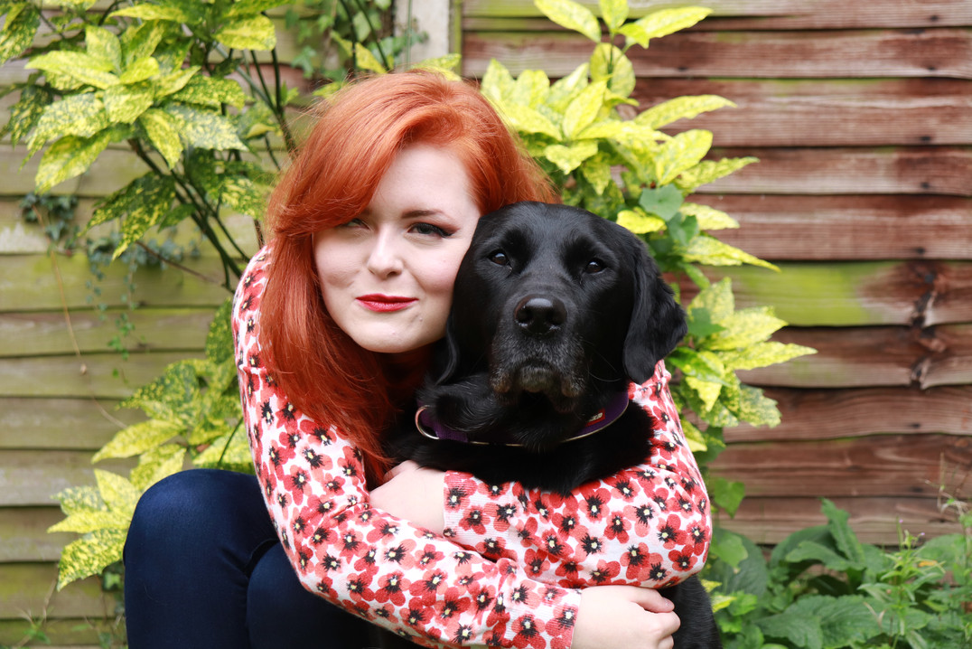 Lucy is hugging black labrador cross retriever Olga the guide dog in the garden. She is wearing a poppy patterned cardigan and royal blue skinny jeans. They are both looking at the camera and Lucy is making a silly squinting face.