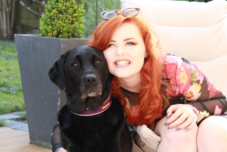 Lucy Edwards cuddling her black guide dog Olga