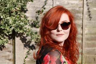 Lucy in a floral dress wearing sunglasse