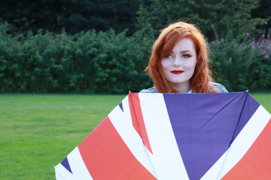 Lucy Edwards looking at the camera whilst holding a union jack umbrella in front of her torso close up