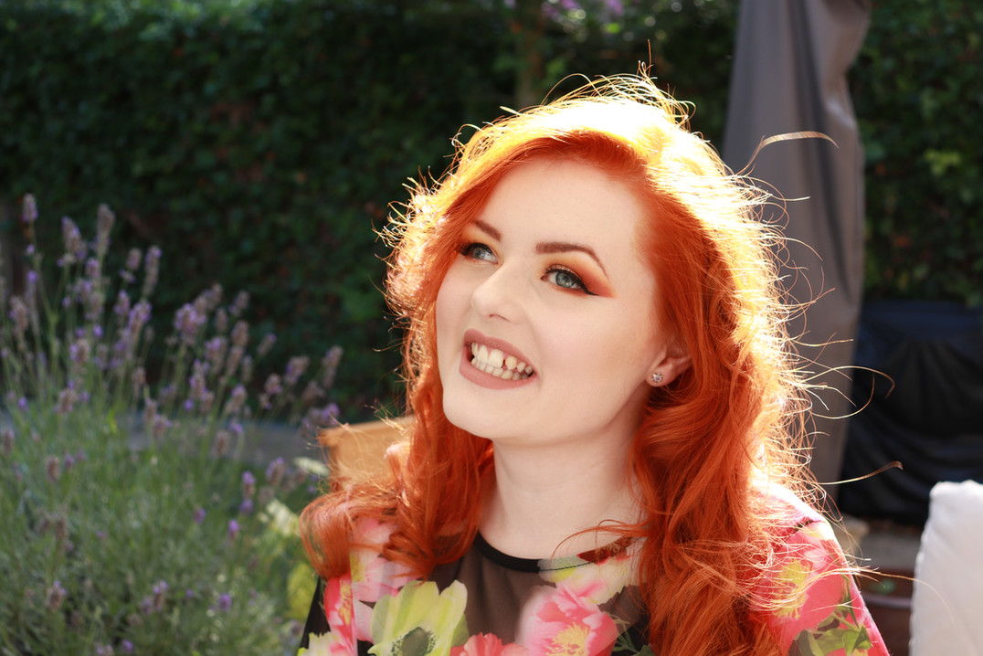 Lucy Edwards tilting her head and smiling at the camera in the garden