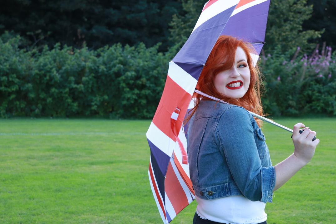 Lucy Edwards smiling in a denim jacket holding a union jack umbrella over her shoulder wider shot