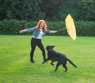 Olga the black labrador runs towards Lucy who is wearing a denim jacket and a white top. She holds, outstretched a yellow umbrella
