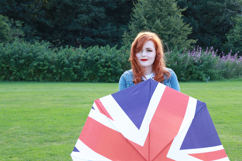 Lucy Edwards looking at the camera whilst holding a union jack umbrella in front of her torso