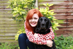 Lucy is hugging black labrador cross retriever Olga in the garden. She is wearing a poppy patterned cardigan and royal blue skinny jeans. They are both looking at the camera and Lucy is smiling.