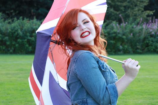 Lucy Edwards smiling in a denim jacket holding a union jack umbrella over her shoulder