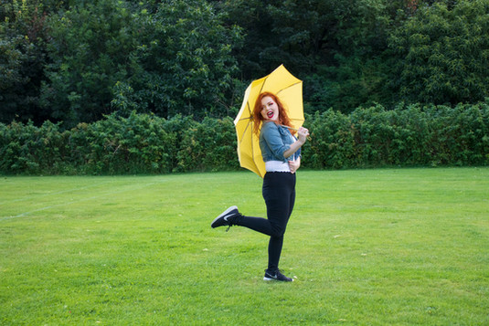 Lucy in a denim jacket holding a yellow umbrella. She is kicking out her right leg behind her