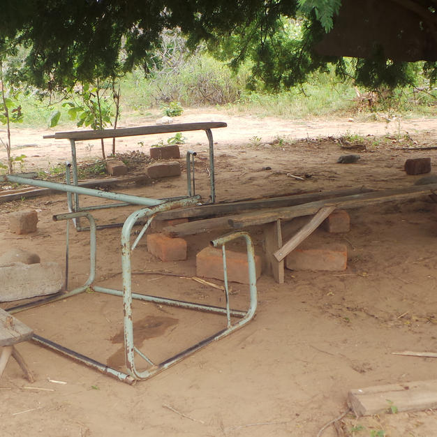Children sat at broken desks under a tree