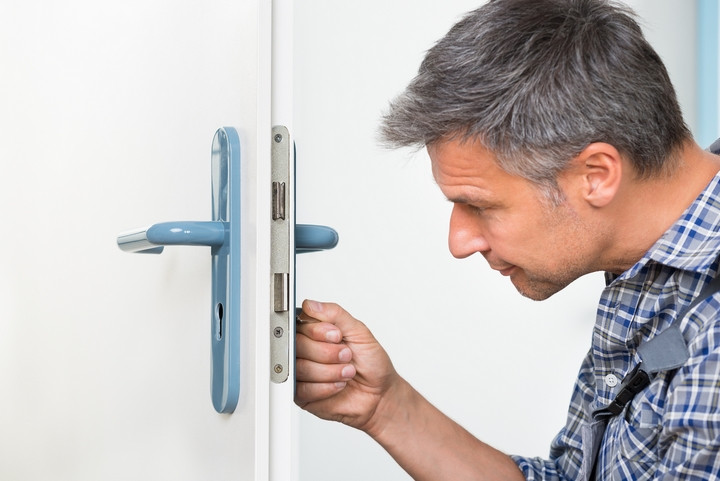 A Professional Locksmith Fixing a Door Lock