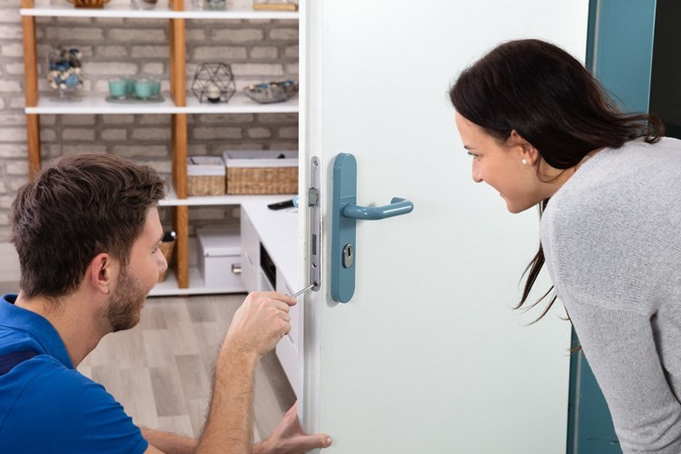 A Professional Locksmith Helping the Homeowner By Fixing the Door Lock