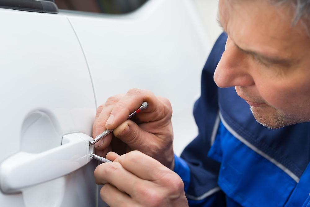 A Professional Car Locksmith Fixing a Car Lock