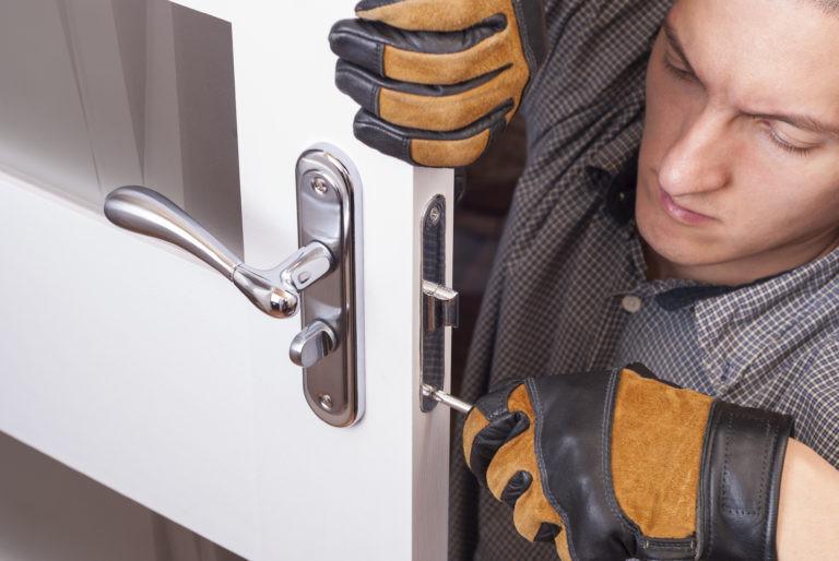 A Professional Locksmith Fixing the Door Lock