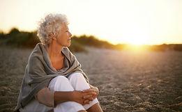 Mature-woman-on-beach-looking-into-horiz