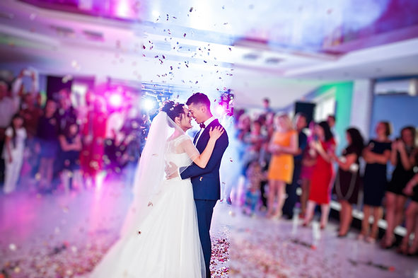 Touching and emotional first dance of the couple on their wedding with confetti and colorf