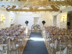 Pastel pink chair drapes with faux flowers hired for a wedding at Rockbeare Manor.