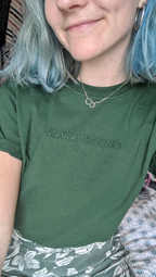 female takes a selfie while wearing a green swearing is cool unfuck the planet tshirt
