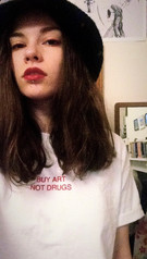 female takes a selfie while wearing a white swearing is cool and little big art buy art not drugs tshirt and big black hat while in a bedroom
