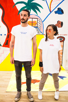 female wears white swearing is cool and little big art buy art not drugs tshirt while gazing at male wearing create culture not drama tshirt in art gallery with red artwork in the background