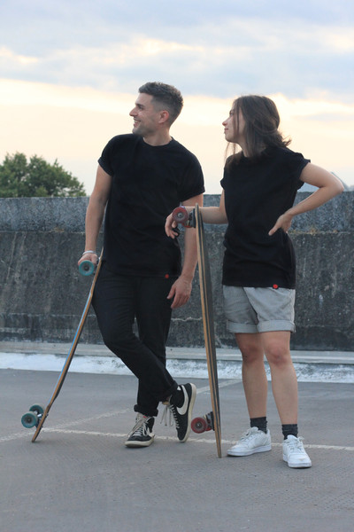 male and female wear black swearing is cool t-shirt while holding skateboards on top of a car park in cardiff
