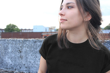 female wears black swearing is cool t-shirt on top of a car park in cardiff