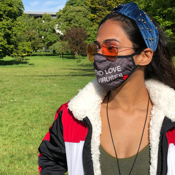 female wears grey swearing is cool spread love not viruses face mask in the park with red glasses, green crop top and blue jacket