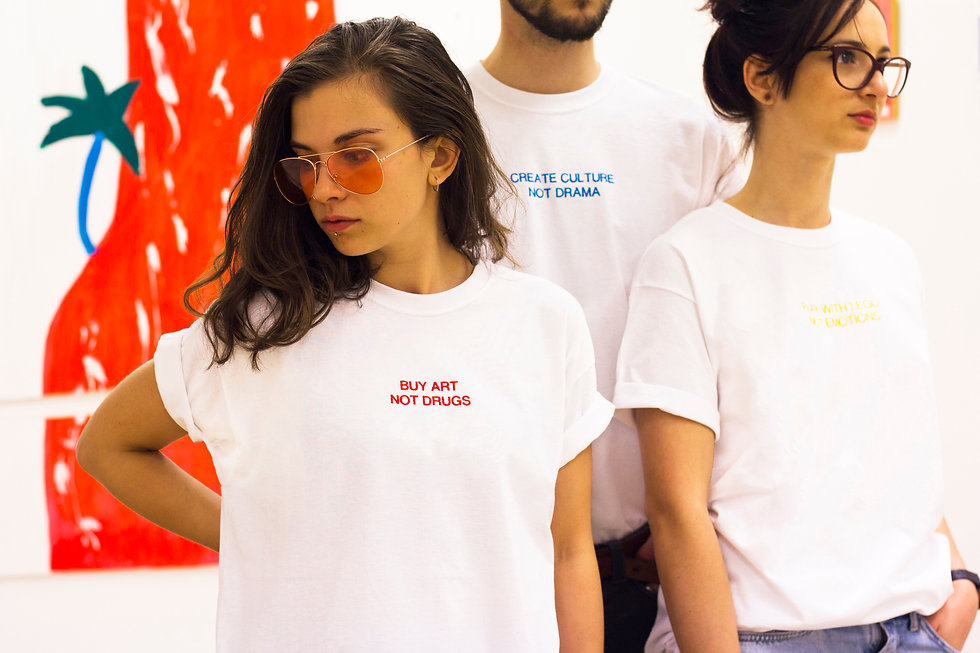 female wearing white swearing is cool buy art not drugs tshirt with male wearing white create culture not drama tshirt with female wearing play with lego not emotions tshirt in an art gallery with red awrwork in the background