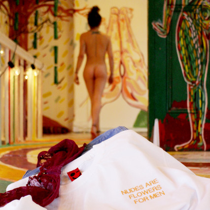 nude female walks away from a pile of clothes with white swearing is cool nudes are flowers for men tshirt, jeans, and red underwear, in art gallery with green door
