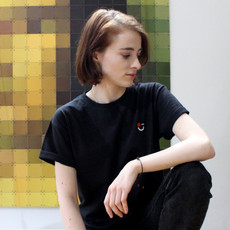 female wears black swearing is cool logo tshirt and black jeans while staring to the side. pixelated mona lisa in the background