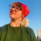 confused female wears green swearing is cool unfuck the planet tshirt while staring at the sky while wearing a red bandana and glasses