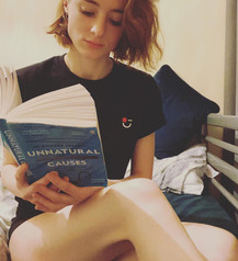 female wears black swearing is cool logo tshirt with her legs exposed while reading sat in bed
