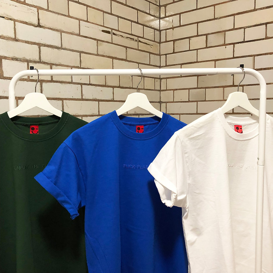 three swearing is cool tshirts hanging on a rail. tshirts are green unfuck the planet and blue fuck plastic and white zero fucking chill tshirt with a brick tile background