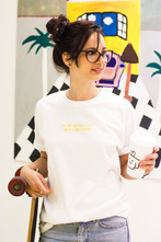 female wears white swearing is cool and little big art buy play with lego not emotions tshirt in art gallery with artwork in the background