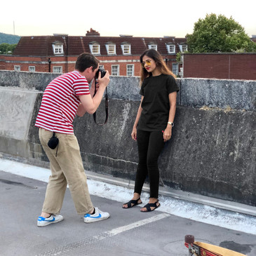 female wears black swearing is cool t-shirt while being photographed on a photoshoot on top of a car park in cardiff