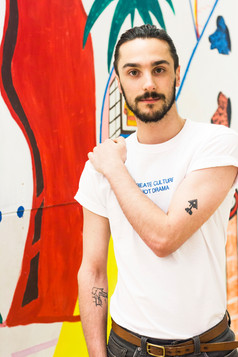 male wears white swearing is cool and little big art create culture not drama tshirt in art gallery with artwork in the background