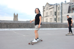 male and female wear black swearing is cool t-shirt while skateboarding on top of a car park in cardiff