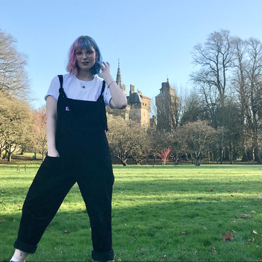 female wears white swearing is cool small titties big heart tshirt in black lucy & yak dungarees while in the park with cardiff castle in the background