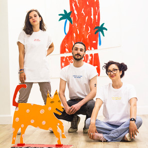 female wears white swearing is cool and little big art buy art not drugs tshirt with female wearing white play with lego not emotions tshirt and male wearing create culture not drama tshirt in art gallery with red artwork in the background