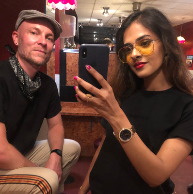male and female wear black swearing is cool t-shirt while taking a selfie in a bar in cardiff