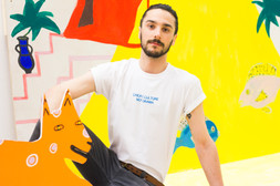 male wears white swearing is cool and little big art create culture not drama tshirt in art gallery with yellow artwork in the background